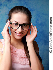 Beautiful woman in glasses looking happy on blue background