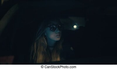Beautiful woman in glasses sits in the car and uses the application on the smartphone at night