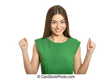 Beautiful woman in green dress gesturing winner sign isolated
