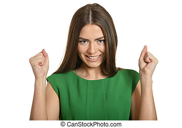 Beautiful woman in green dress gesturing winner sign on white background