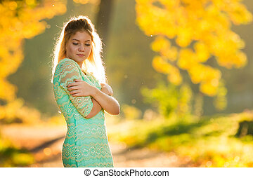 Beautiful Woman in green dress on Fall Nature Background