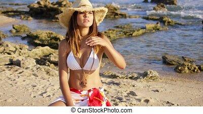 Beautiful woman in hat and bikini near ocean