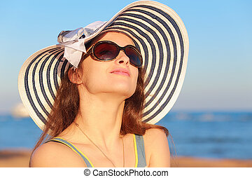 Beautiful woman in hat and sun glasses looking up and joy on blue sea background