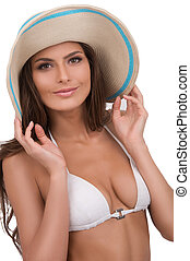 Beautiful woman in hat. Attractive young woman in bikini looking at camera and adjusting her hat while standing isolated on white