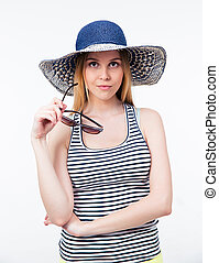 Beautiful woman in hat holding glasses