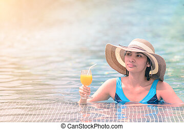 Beautiful woman in hat is holding orange juice glass at poolside in summer.