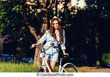 woman in hat posing with bike