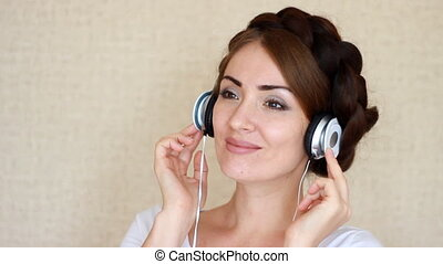 Beautiful woman in headphones listening to a musical song on light background.