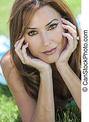 Outdoor portrait of a beautiful young brunette woman in her thirties relaxing on her hands.