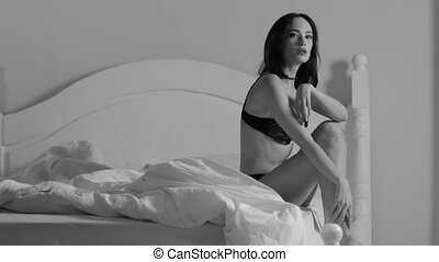 Beautiful woman in her underwear is sitting on the bed. Black and white shooting. White linen. High quality 4k footage.