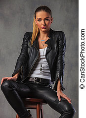 woman in leather jacket posing seated on stool in studio
