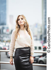 Beautiful woman in leather skirt posing on the street