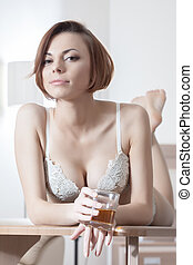 Beautiful woman in lingerie with alcohol drink