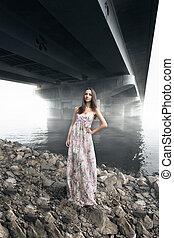 woman in long dress posing under bridge at foggy day - ...