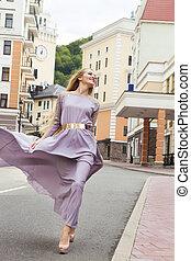Beautiful woman in long dress walking outdoors