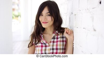 Beautiful woman in long hair smiling with hand up near...