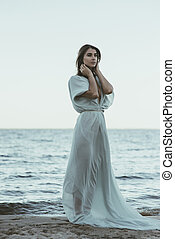 Beautiful woman in long white flowing dress standing on the beach