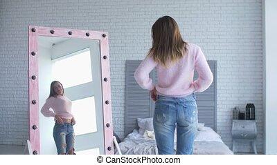 Beautiful woman in loose pants admiring body shape