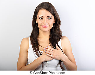 Beautiful woman in love holding herself chest and heart two hands with enjoying smiling face and thinking about emotion relationship. Closeup portrait