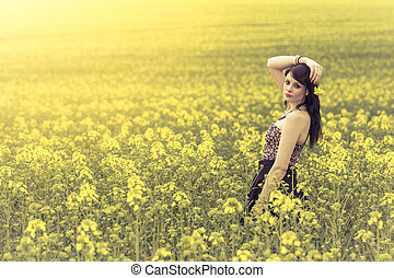 Beautiful woman in meadow of yellow flowers with arm up
