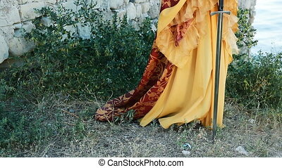 Beautiful woman in medieval dress with sword - Young woman...