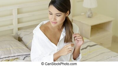 Beautiful woman in night shirt sitting on bed - Single...