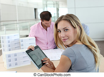 Beautiful woman in office using electronic tablet