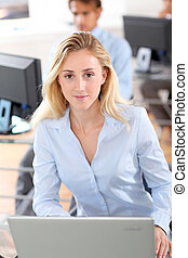 Beautiful woman in office working on laptop computer