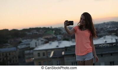 Beautiful woman in orange t-shirt and shorts taking selfie...