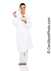 beautiful woman in pajamas eating green salad