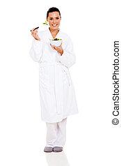 beautiful woman in pajamas eating green salad