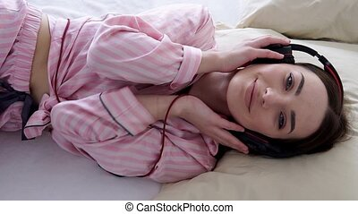 beautiful woman in pajamas lies and listens to music with headphones