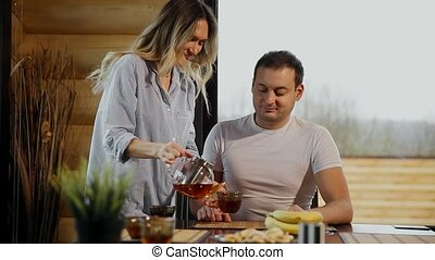 Beautiful woman in pajamas pours her husband tea, hugging him in the kitchen and drink tea. Lovers.