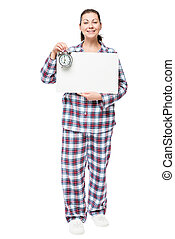 Beautiful woman in pajamas with a poster and an alarm clock before going to bed on a white background
