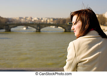 Beautiful woman in Paris on the Seine embankment, contemplating the river, thoughtful