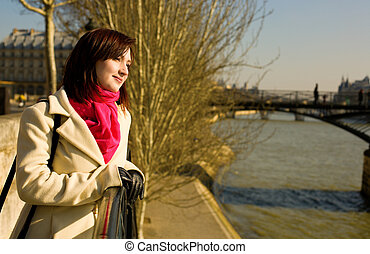 Beautiful woman in Paris on the Seine embankment near the pedestrian bridge Pont des Arts