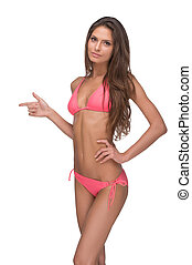 Beautiful woman in pink bikini. Attractive young woman in bikini looking at camera and pointing away while standing isolated on white