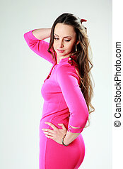 Beautiful woman in pink dress standing on gray background
