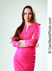 Beautiful woman in pink dress with arms folded standing on gray background