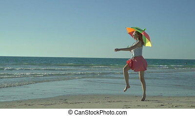 Beautiful woman in pink skirt with sunglasses is jumping on the beach. Happy girl jumps with rainbow umbrella. Slow motion