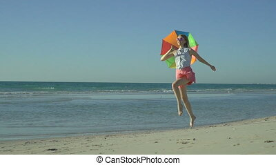 Beautiful woman in pink skirt with sunglasses is running and jumping on the beach. Happy girl jumps with rainbow umbrella, enjoys her summer vacation. Slow motion