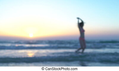 Beautiful woman in pink swimsuit is running to sun on the beach, sits at sea or ocean. Happy girl runs to sunset, splashes waves, rejoices, enjoys her summer vacation, dancing in water. Slow motion