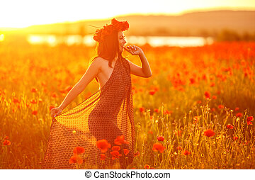 beautiful woman in poppy field at sunset