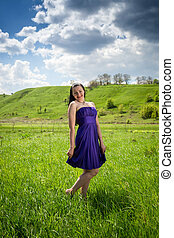 Beautiful woman in purple dress walking at meadow at sunny day