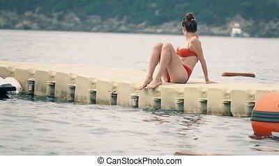 Beautiful woman in red bikini sits on floating pontoon at sea