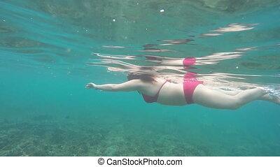 beautiful woman in red bikini swimming underwater slow motion