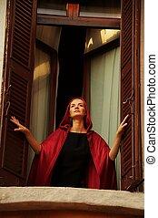 Beautiful woman in red cloak in a window.