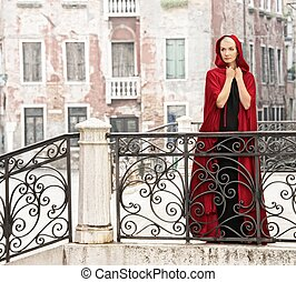 Beautiful woman in red cloak on a bridge.