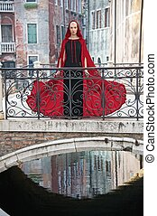 Beautiful woman in red cloak on a bridge