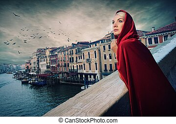 Beautiful woman in red cloak on a bridge.